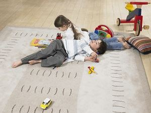 Children playing on secured rug